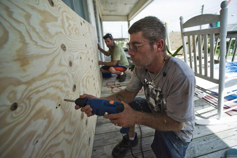 Doug Gray (R) and Daniel Wickoff board up a sliding glass door on a beachside home as they prepare for Hurricane Irene in Atlantic Beach, North Carolina