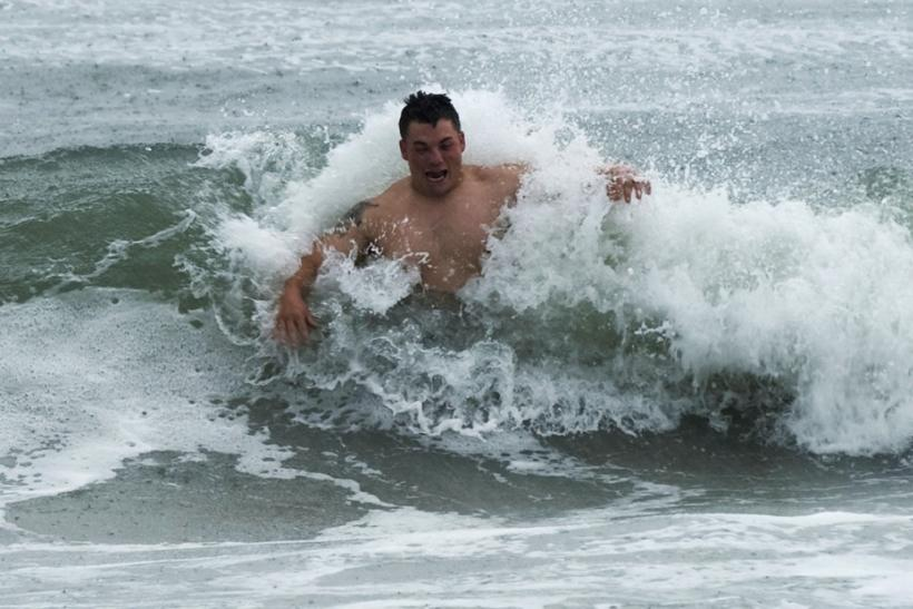 A swimmer braves the shore break as feeder bands from Hurricane Irene begin to pound Atlantic Beach, North Carolina