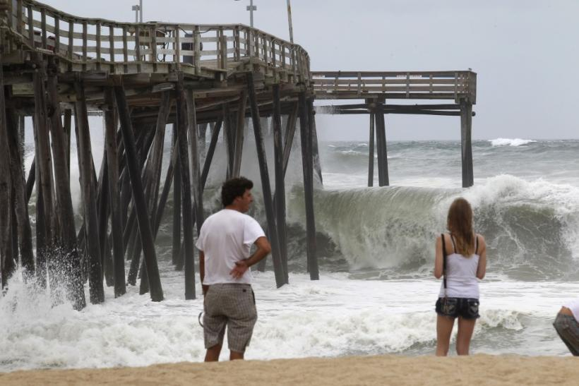 Residents look on as waves hit the pier at Cape Hatteras National Seashore in Avon, North Carolina