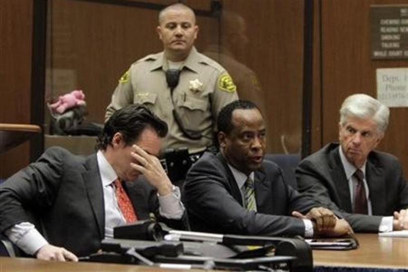 Doctor Conrad Murray (C), the late Michael Jackson's personal physician, sits with his lawyers Edward Chernoff (L) and Michael Flanagan during his arraignment on a charge of involuntary manslaughter in the pop star's death, in Los Angeles, Calif