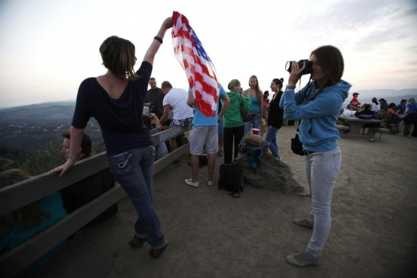 A woman holds a U.S. flag while posing for a photo as she waits for Independence Day fireworks in Los Angeles