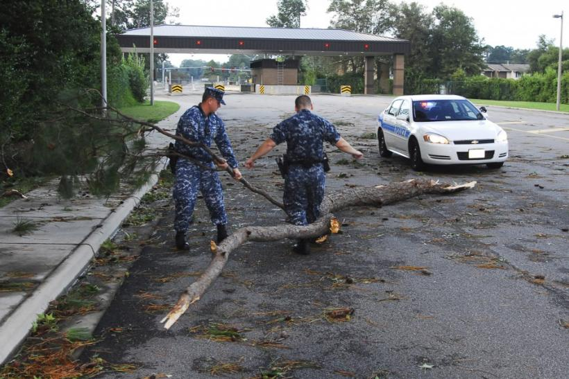 Sailors move debris from Hurricane Irene at an entrance to Joint Expeditionary Base Little Creek-Fort Story in Virginia Beach