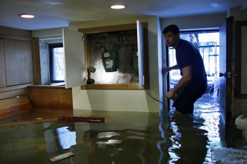 American-Russian Kozlov walks through his flooded basement after the pass of Hurricane Irene at Hoboken