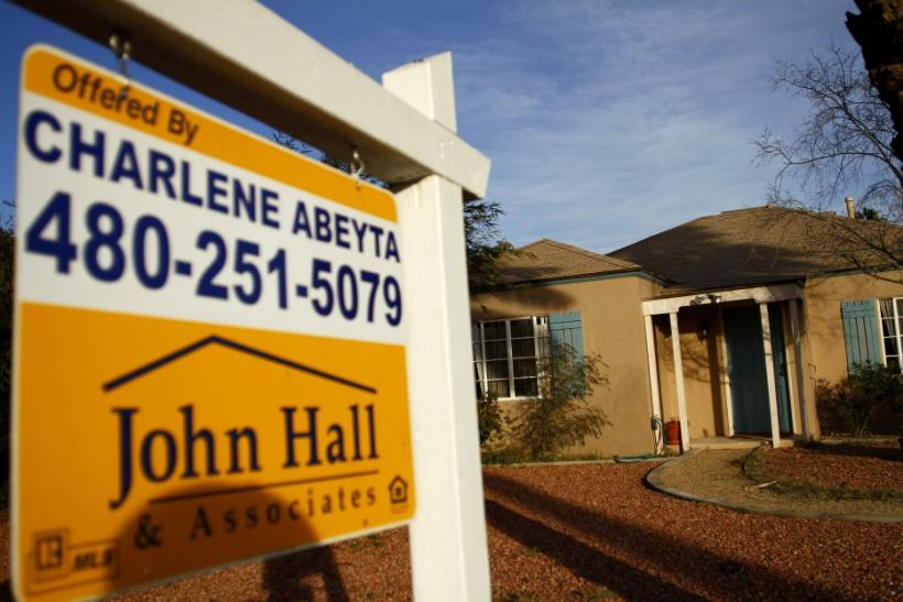 A realtor sign is displayed near a house for sale in Phoenix