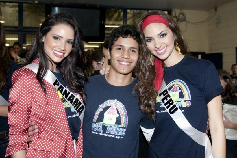 Miss Panama Sheldry Saez and Miss Peru Natalie Vertiz pose with a boy at Casa Do Zezinho social project for slum children, in Sao Paulo