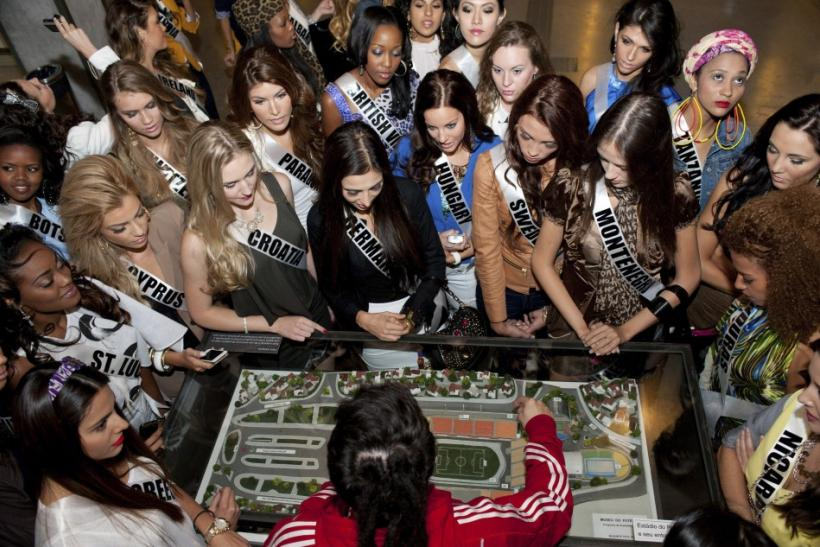 Candidates for the Miss Universe 2011 competition stand around a model of a stadium during a visit to the Futbol (Soccer) Museum in Sao Paulo