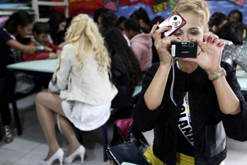 Miss Poland 2011 Rozalia Mancewicz takes a photograph at the Casa do Zezinho, a non-governmental organization in Sao Paulo