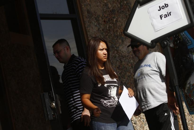 A woman exits a job fair at the Phoenix Workforce Connection as others wait to enter in Phoenix