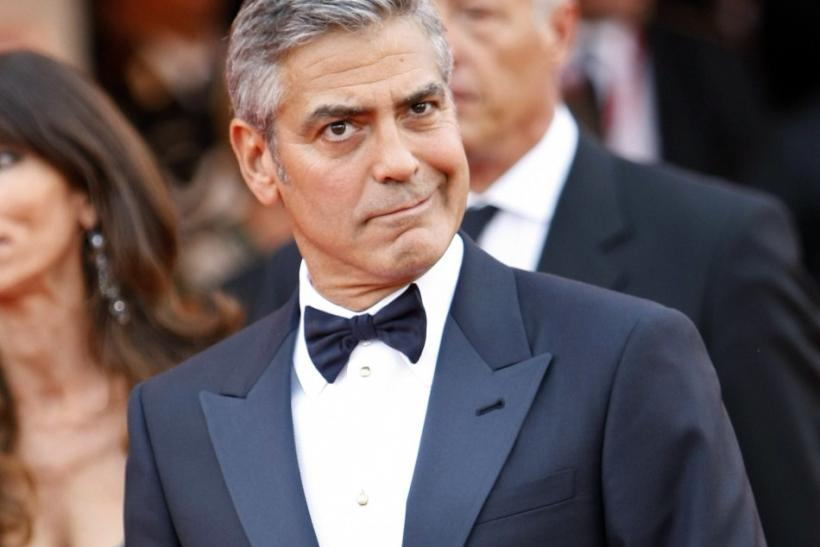 "U.S. actor George Clooney makes a face as he arrives on the ""The Ides of March"" red carpet at the 68th Venice Film Festival in Venice"