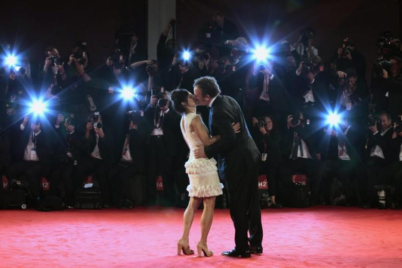 "Actor John C. Reilly (R) kisses his wife Alison Dickey as they pose for photographers on the ""Carnage"" red carpet at the 68th Venice Film Festival in Venice"
