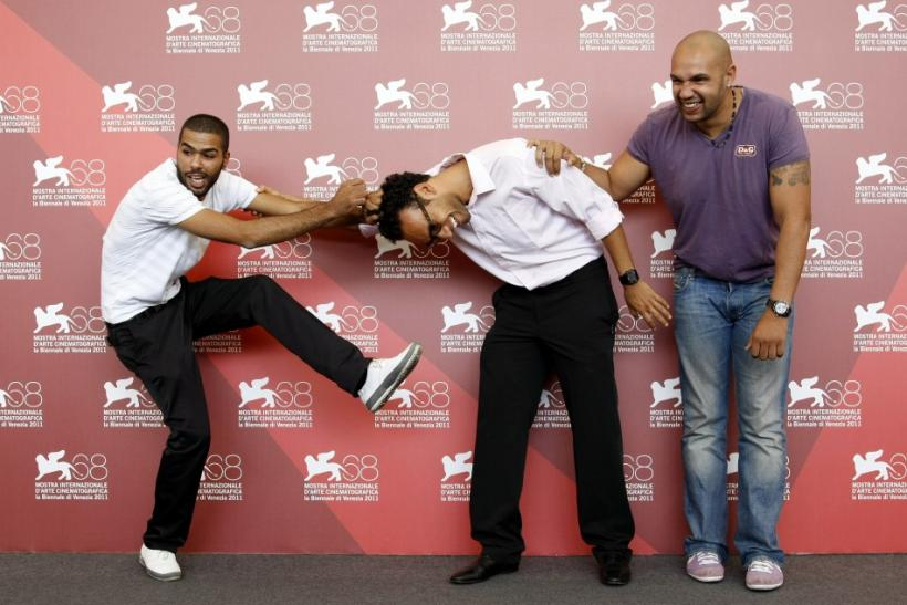 "Actors Rashid Debbouze (L), Yassine Azzouz (C) and Kamel Laadaili joke during a photocall for the movie ""La Desintegration"" at the 68th Venice Film Festival"