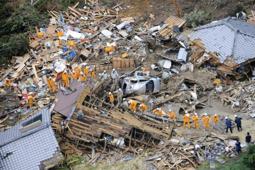 An aerial view shows firefighters searching among collapsed houses following a landslide caused by strong tropical storm Talas in Tanabe, in western Japan