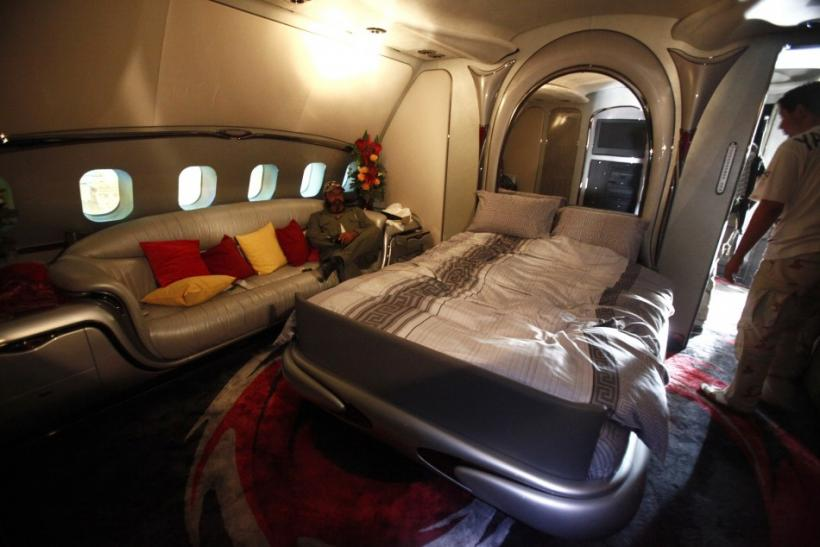 A Libyan rebel fighter sits in a bedroom of Muammar Gadhafi's private plane, at the international airport in Tripoli August 28, 2011.