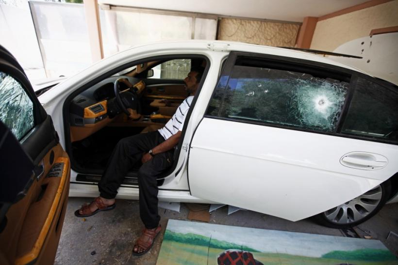 A Libyan sits inside an armoured car at a house belonging to Muammar Gaddafi's son Hannibal in Tripoli August 30, 2011.