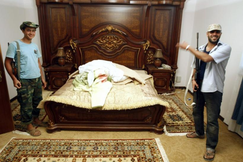 Anti-Gaddafi forces stand next to a bed at Muammar Gadhafi's farm house near the town of Abu Grein some 138km (86 miles) in the last remaining stronghold of Muammar Gaddafi, at the west of Sirte August 30, 2011