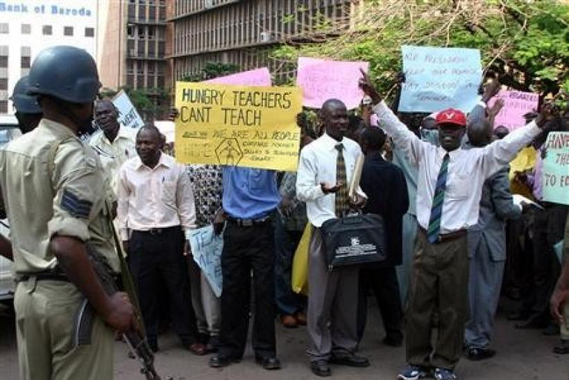 Ugandan primary school teachers hold banners and shout slogans during a demonstration in Kampala