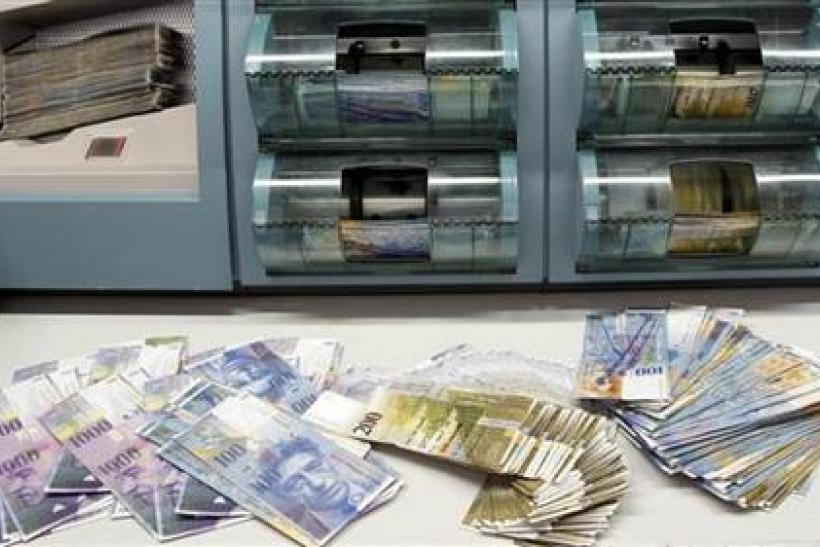 Swiss franc banknotes of several values are sorted in a money counter in a bank in Zurich