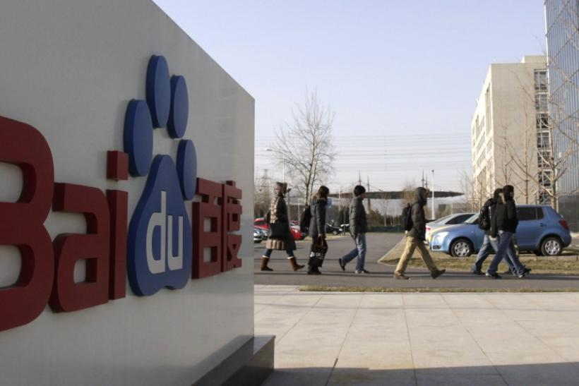 Employees walk past the logo of Baidu outside its headquarters in Beijing
