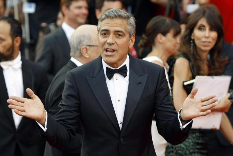 "U.S. actor Clooney gestures as he arrives on ""The Ides of March"" red carpet at the 68th Venice Film Festival"