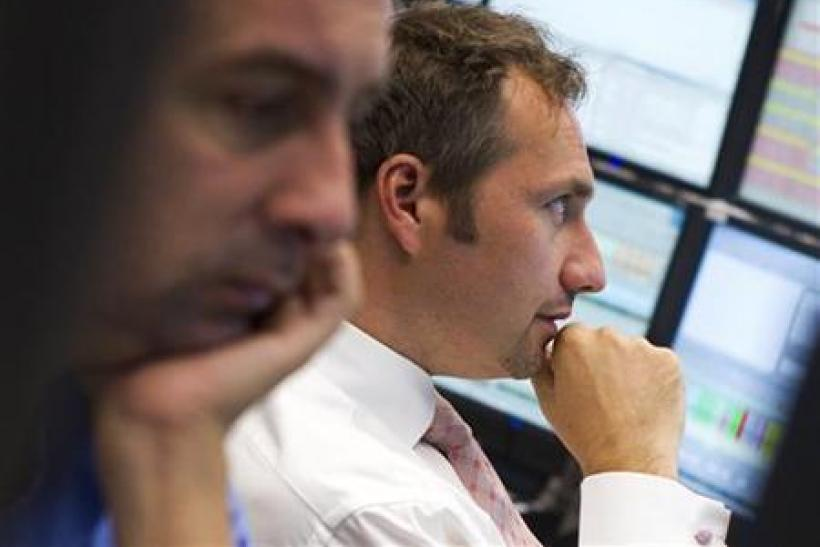 Trader react at their desks at the Frankfurt stock exchange
