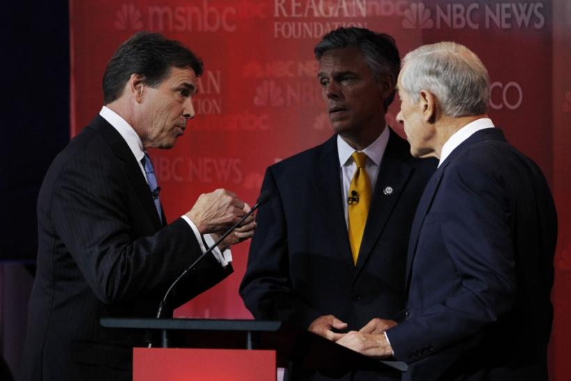 Republican presidential candidates Perry, Paul and Huntsman talk during a break in the presidential primary debate