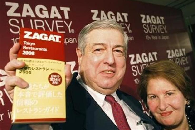 Zagat Survey co-founders Tim (L) and Nina Zagat pose with the latest version of their guide to Tokyo restaurants at a news conference in Tokyo