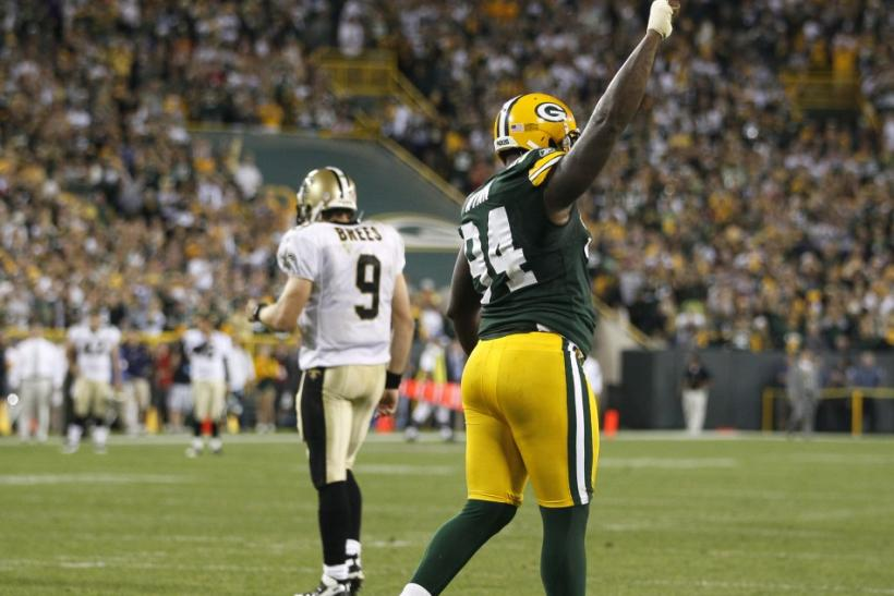 Packers Walden celebrates after the final play of the game as New Orleans Saints quarterback Drew Brees walks off the field during their NFL football game in Green Bay