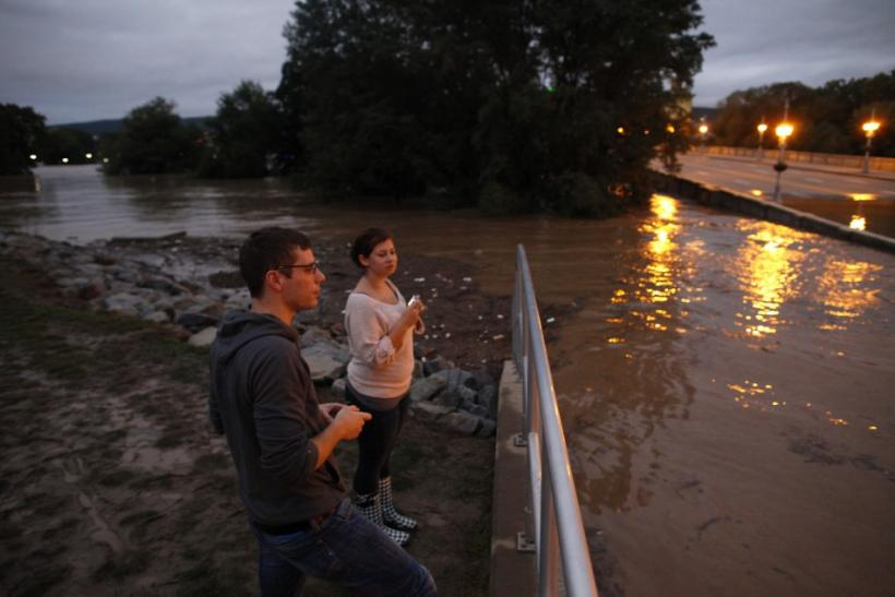 Joe Senchak and Jenis Walsh stand at a flood wall on the Susquehanna River in Kingston