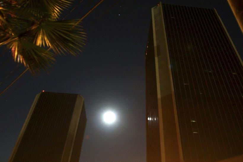 The moon shines behind buildings during a power outage in downtown Tijuana
