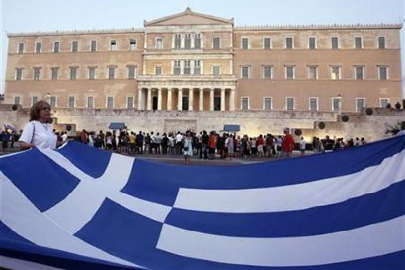 Protester holds giant Greek national flag in front of parliament building during rallyn in Athens' Syntagma square