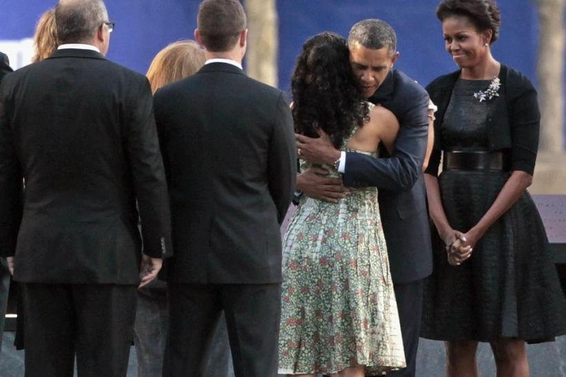U.S. President Barack Obama embraces victims' family members as first lady Michelle Obama stands by at the 9/11 Memorial during the tenth anniversary ceremonies at the World Trade Center site in New York