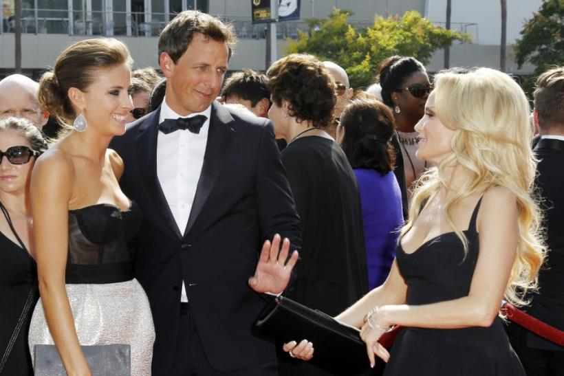 Actor Seth Meyers (C) and Alexi Ashe (L) talk with actress Kristin Chenoweth (R) as they arrive at the 2011 Primetime Creative Arts Emmy Awards in Los Angeles