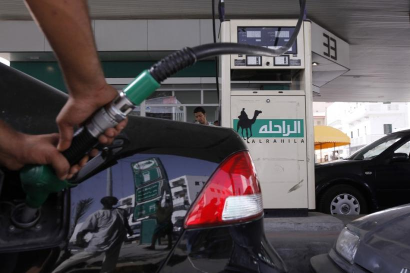 A man fills up the tank of a car at a petrol station in Tripoli