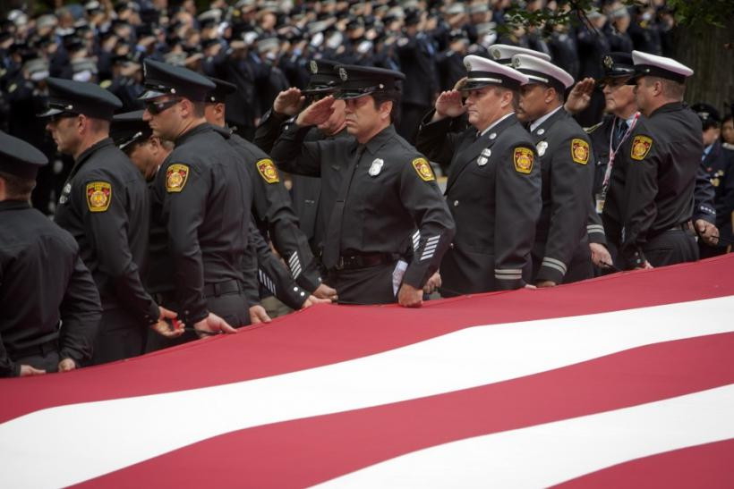Los Angeles firemen salute as they hold a large American flag during a ceremony honoring firefighters and public servants killed in the 9/11 attacks on the World Trade Center, on the 10th anniversary, in New York