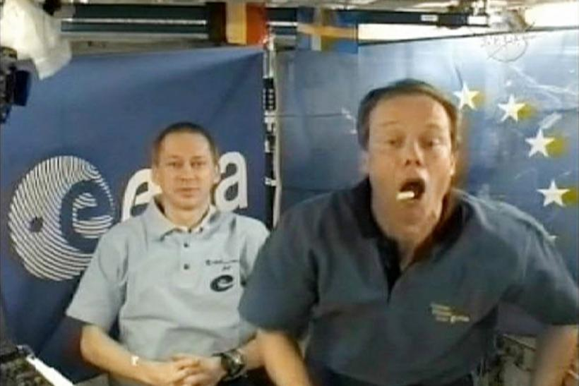 European Space Agency astronaut Christer Fuglesang catches some food in his mouth as fellow ESA astronaut Frank De Winne looks on