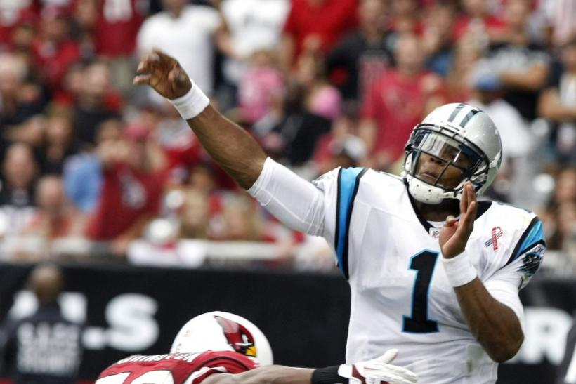 Panthers' Newton throws down field as he is tackled by Panthers' Davis in their NFL football game in Glendale