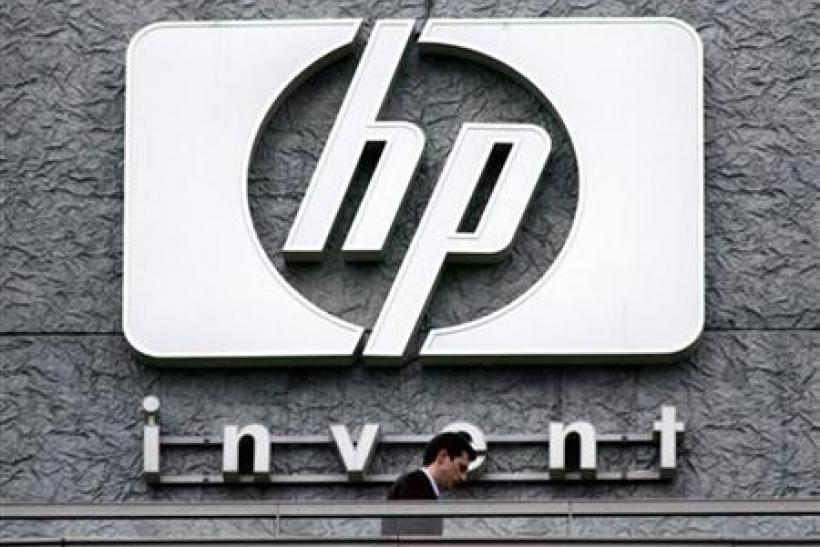 File photograph of a man walking past the Hewlett Packard logo at its French headquarters in Issy le Moulineaux