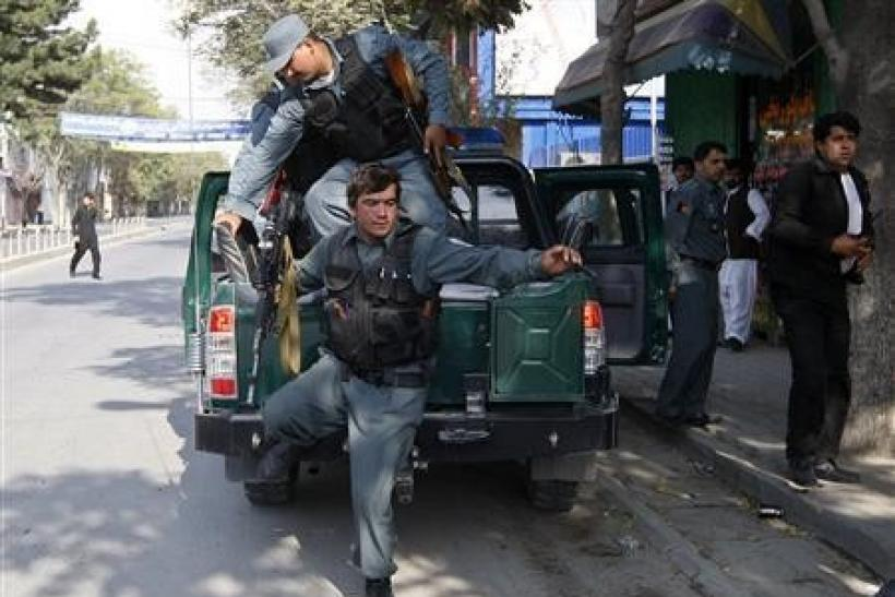 Afghan policemen arrive at the site of a rocket-propelled attack in Kabul