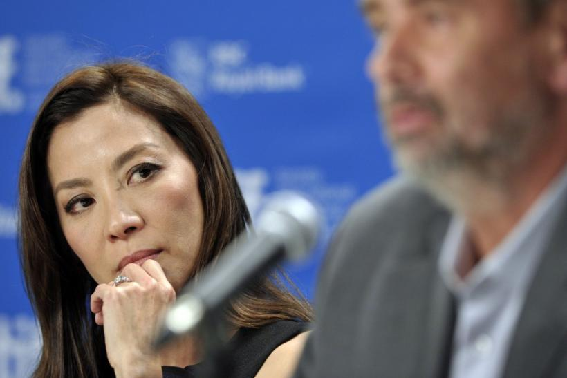 "Malaysian actress Yeoh listens to French director Besson speak during news conference for film ""The Lady"" at 36th Toronto International Film Festival"