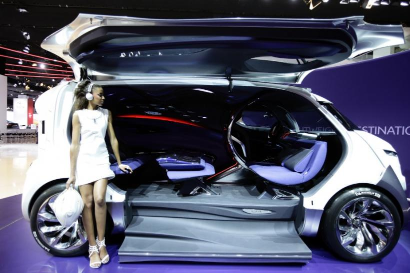 A model poses at the exhibition booth of French carmaker Citroen next to the new 'Tubik' car during the International Motor Show (IAA) in Frankfurt