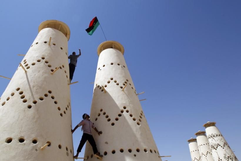 Anti-Gaddafi fighters climb in a pigeon farm in Gaddafi house compound in Assdada Fort