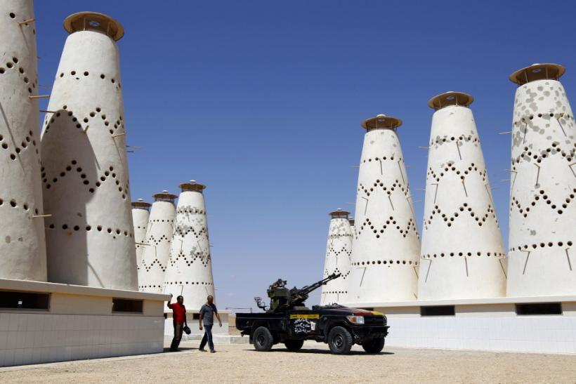 Anti-Gaddafi fighters walk in a pigeon farm in Gaddafi house compound in Assdada Fort