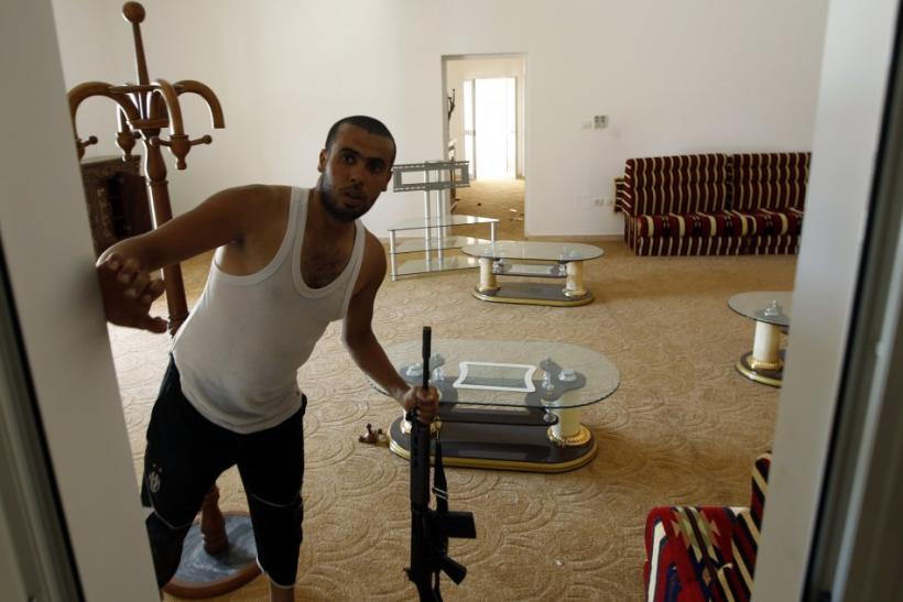 An anti-Gaddafi fighter holds a rifle in Gaddafi house in Assdada Fort