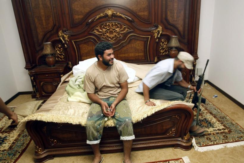 Anti-Gaddafi forces sit on a bed at Muammar Gaddafi's farm house