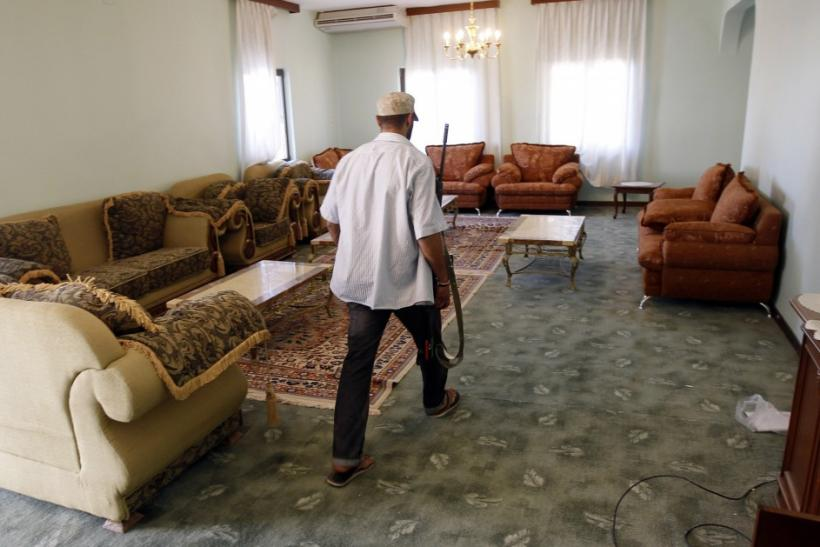 An anti-Gaddafi fighter walks inside Muammar Gaddafi's farm house near the town of Abu Grein