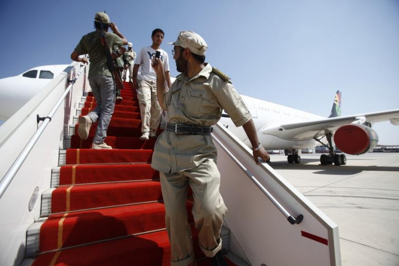 A Libyan rebel fighter takes a photo of Muammar Gaddafi's private plane