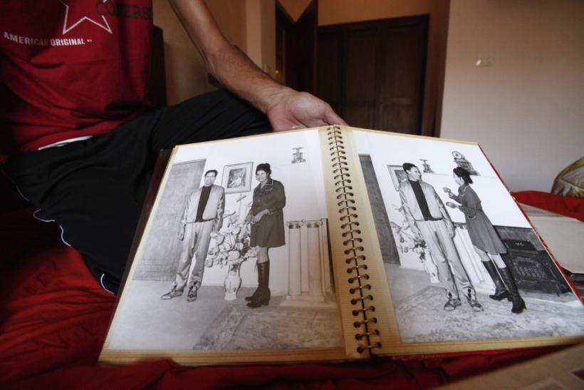 A Libyan rebel fighter shows photographs of Muammar Gaddafi with his wife Safiya Farkache