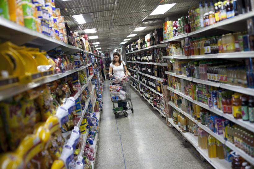 A woman looks at groceries at a supermarket in Caracas