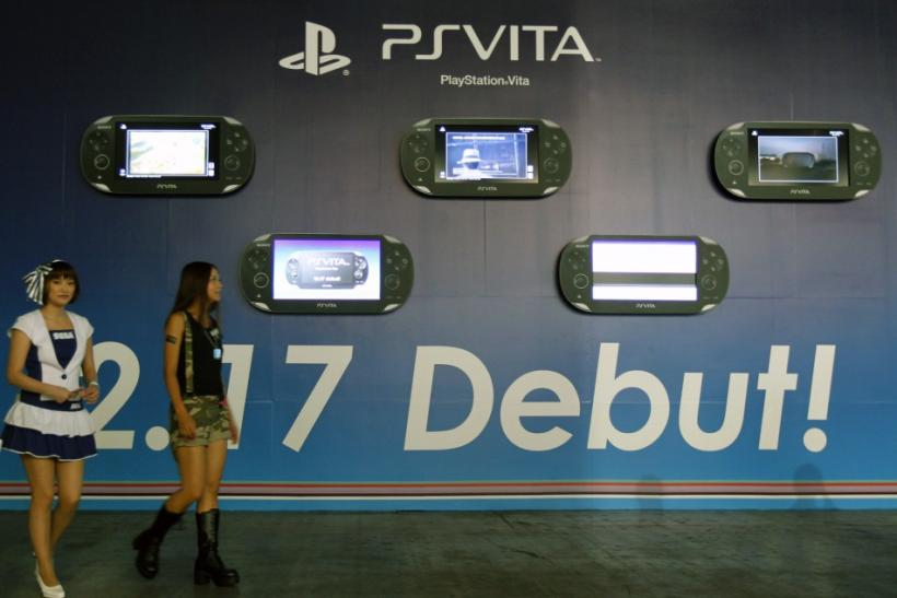 Promoters dressed as video game characters walk past an advertisement board of Sony's PlayStation Vita handheld gaming device at Tokyo Game Show in Chiba, east of Tokyo