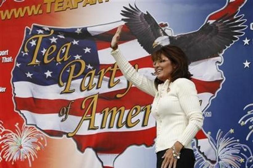 Former Governor of Alaska Sarah Palin waves to supporters at a rally organized by the Tea Party of America in Indianola, Iowa